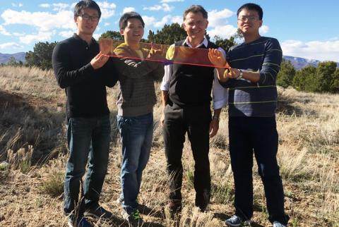 Los Alamos Center for Advanced Solar Photophysics researchers hold a large prototype solar window. From left to right: Jaehoon Lim, Kaifeng Wu, Victor Klimov, Hongbo Li.