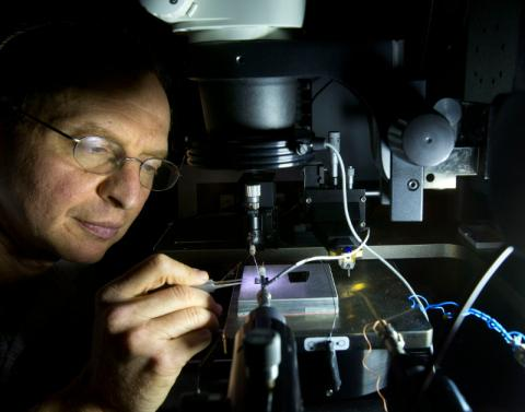 Sandia National Laboratories researcher Alec Talin inspects a plasmonic array sample using a probe station microscope. Photo by Dino Vournas